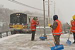Merrick, New York, U.S. January 21, 2014. Pausing briefly for safety's sake as a train enters the LIRR Merrick Train Station, Maintenance of Way (MOW) workers for the Metropolitan Transit Authority (MTA) shovel snow as it falls heavily on the windy elevated platform. The Metropolitan Transit Authority added extra afternoon trains to Long Island Rail Road. Governor Cuomo declared a state of emergency due to the snow storm, with up to 10 inches of snow expected.