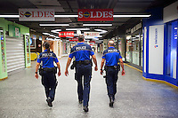 Switzerland. Geneva. Thee police officers patrol on feet at night the underground shopping mall of the railway station. Sign for sales season. The police woman and both policemen are wearing a ballistic vest, bulletproof vest or bullet-resistant vest which is an item of personal armor that helps absorb the impact from knives, firearm-fired projectiles and shrapnel from explosions, and is worn on the torso. Soft vests are made from many layers of woven or laminated fibers and can be capable of protecting the wearer from small-caliber handgun and shotgun projectiles. The policewoman haa a two-way radio which is a radio that can both transmit and receive (a transceiver). A two-way radio (transceiver) allows the operator to have a conversation with other similar radios operating on the same radio frequency (channel). Two-way radios are available with hand-held portable configurations. Hand-held radios are often called walkie-talkies or handie-talkies. They all carry  a Glock pistol which is a semi-automatic pistol designed and produced by Glock Ges.m.b.H. 9.07.12 &copy; 2012 Didier Ruef?.