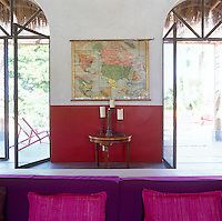 In the living the French windows lead onto a terrace shaded by an awning of palm fronds while inside the walls and furnishings are in vibrant reds and purples