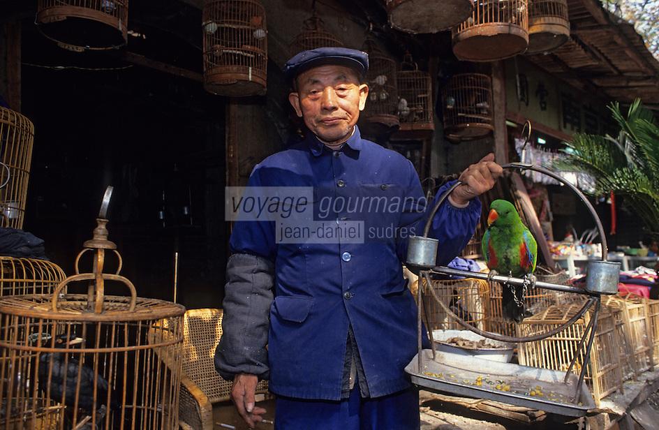 Asie/Chine/Jiangsu/Nankin/Quartier du temple de Confucius&nbsp;: March&eacute; aux oiseaux - Marchand pr&eacute;sentant un perroquet<br /> PHOTO D'ARCHIVES // ARCHIVAL IMAGES<br /> CHINE 1990