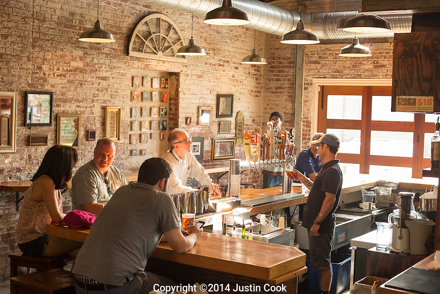 DURHAM, N.C. Tuesday August 5, 2014 - Patrons enjoy drinks just before the dinner rush at Geer Street Garden, a renovated service station, in Durham, N.C. (Justin Cook for The New York Times)