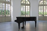 A solitary grand piano stands in the middle of this contemporary gallery with original 18th century windows opening onto the courtyard