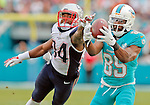 Miami Dolphins wide receiver Greg Jennings (85) hauls in a long pass from Miami Dolphins quarterback Ryan Tannehill (17) as New England Patriots cornerback Leonard Johnson (34) defends in the second quarter as the Miami Dolphins host the New England Patriots at Sun Life Stadium on Sunday, January 3, 2016
