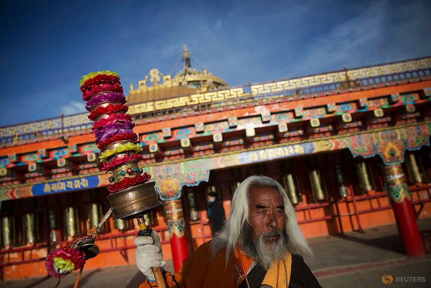 Padma Tsering, a populat Tibetan Buddhist monk spins his prayer wheels at a monastery above the Larung Wuming Buddhist Institute, located some 3700 to 4000 metres above the sea level in remote Sertar county, Garze Tibetan Autonomous Prefecture, Sichuan province, China October 30, 2015. The Institute was founded in 1980 by Khenpo Jigme Phuntsok, an influential lama of Nyingma sect of Tibetan buddhism with only around 30 students but is now widely known as one of the biggest centres to study Tibetan Buddhism in the world. Today, tens of thousands monks and nuns live in small houses and log cabins surrounding the Larung Wuming Buddhist Institute. Picture taken October 30, 2015.   REUTERS/Damir Sagolj
