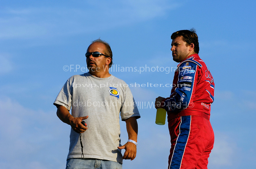 Danny Lasoski (L) and Tony Stewart watch qualfying from the top of their transporter.