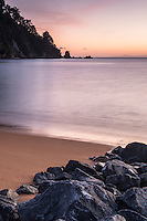 Sun rises on golden beach in Totaranui, Abel Tasman National Park, Nelson Region, New Zealand