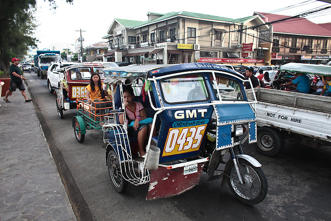 A throng of motorcycle rickshaws and other vehicles create a late afternoon traffic jam on the seaside boulevard of Dumaguete, Negros island, Philippines. June 16, 2011.