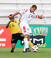 Jevani Brown (14) of Jamaica tries to tackle the ball away from Roberto Chen (5) of Panama during the third place game of the CONCACAF Men's Under 17 Championship at Catherine Hall Stadium in Montego Bay, Jamaica. Panama defeated Jamaica, 1-0.