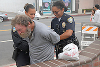 Two Santa Monica Police Officers arrest a man at the Main Street Farmers Market for a alcohol related offence on Sunday, September 19, 2010.