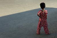 Street scene,a child on the road shadow and light, near Bollywood area, Mumbai India