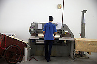 "An Amity Printing Company employee trims reams of Bible pages after printing in the Amity Printing Company's new printing facility in Nanjing, China....On May 18, 2008, the Amity Printing Company in Nanjing, Jiangsu Province, China, inaugurated its new printing facility in southern Nanjing.  The facility doubles the printing capacity of the company, now up to 12 million Bibles produced in a year, making Amity Printing Company the largest producer of Bibles in the world.  The company, in cooperation with the international organization the United Bible Societies, produces Bibles for both domestic Chinese use and international distribution.  The company's Bibles are printed in Chinese and many other languages.  Within China, the Bibles are distributed both to registered and unregistered Christians who worship in illegal ""house churches."""