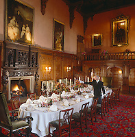 Candles are lit as the finishing touches are made to a table laid for dinner in the Great Hall