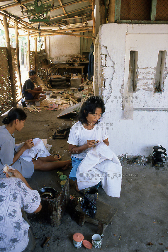 Indonesia, Java island; artisan working on a batik, after preparation of the design,she  applies the wax melted on the parts that do not have to be painted,  so that it penetrates the fibers of the fabric, preventing the waterproof color to adhere; using a tool called a canting ( tjanting).<br />
