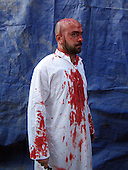 KARBALA, IRAQ: A devout Shia man, is covered in blood after beating himself with a knife on Ashura, the day of mourning for the death of Imam Hussein...Photo by Sami Al-Hilali/Metrography