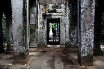 A man stands in a doorway at Ta Prohm in Angkor Thom, Cambodia. June 7, 2013.