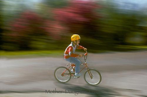 Kid rides red bicycle