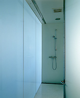 The shower room of a modernised Victorian house is entirely lined in translucent glass with a pale terazzo floor