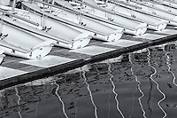 A fleet of double-handed Club 420 sailing dinghies cast reflections in Spa Creek in Annapolis, Maryland.