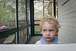 Young Timothy Kirby looks through the screen door of his family's porch.
