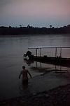 Man goes swimming at dusk in the Amazon River, Peru, South America