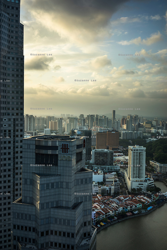 The sun sets upon the Singapore skyline. What does the future of cities look like? I explore Singapore and its continuous vertical development as it tries to balance the urban cityscape of sky scrapers with artificial nature by installing vast green walls on a quest for vertical liveability. Photo by Suzanne Lee/ Panos Pictures