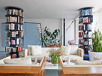 A pair of carousel bookcases stand sentinel beside a seating area comprised of a box sofa and pair of box armchairs by Autoban in the open plan living area