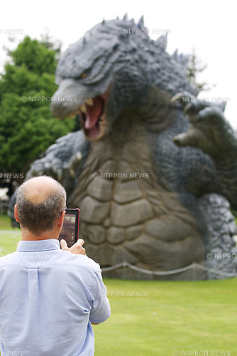 "July 18, 2014, Tokyo, Japan - A man takes pictures of the 6.6 meter model of the new Godzilla at Tokyo Midtown on July 18, 2014, Tokyo. The statue is a 1/7 scale reproduction of the 180 meters tall Hollywood film version of ""GODZILLA"".  Godzilla and its footprints will be displayed from July 18 to August 31 during which time it will perform a special show using mist, light and sound effects every 30 minutes between 19:00 to 21:00. (Photo by Rodrigo Reyes Marin/AFLO)"