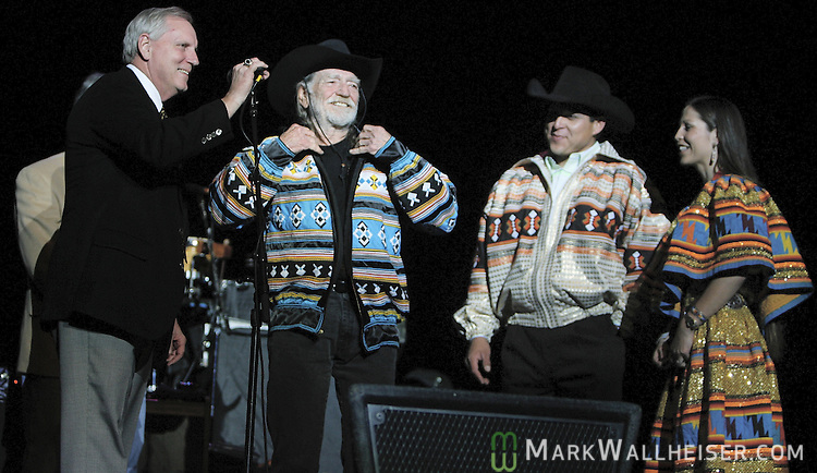 As FSU president TK Wetherall stands at the microphone, Willie Nelson shows off the traditional Seminole jacket he was presented by Na Ha Jumper (3rd from left) and Jo L Jumper (R) with the Siminole Tribe of Florida prior to his concert as part of the 7 Days of Opening Nights at Ruby Diamond Auditorium February 28, 2006.