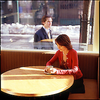 Woman in cafe sitting at table with man walking by outside in background