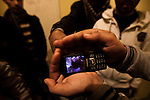 A man plays a video showing the mutilated body of soilders who defected from the army on February 24, 2011. Cell phones movies documenting Qadaffi's abuses and passed secretly around  the country have been instrumental in uniting people against the dictator.