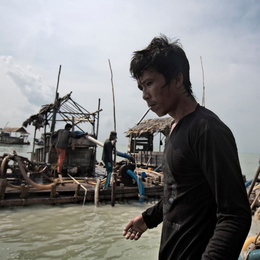 Indonesia - Bangka Island - Rebo - A miner is taking a cigarette break. Around 50 miners work feverishingly on these pontoons from 8am until 5 pm, each one of them earn around 15US$ per day, a much more profitable activity than fishing. Risks of land sliding are extremely high, every year around 60 workers die covered with sand. The turquoise waters have turned brown and muddy and a cloud of black smoke surrounds the pontoons due to the pollution caused by the mining.