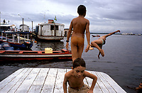 School boys in the Amazon port city of Manaus leap from fishing boats into the Rio Negro below a central city market. The Rio Negro enters the Rio Solimões at Manaus to form the Brazilian Amazon.