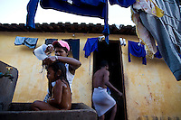 Sugarcane cutter family, migrants from Northeastern Brazil living in a doss-house at Guariba city, in the Ribeirao Preto region, the world greatest productive pole of ethanol and sugar - Sao Paulo State, Brazil -  mother washes daughter in the public concrete wash-tube - mill uniforms hang at clothesline.