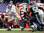 New York Giants quarterback Eli Manning (10) is hauled down from behind by defensive end Seattle Seahawks Cliff Avril (56)  at CenturyLink Field in Seattle, Washington on November 9, 2014. The Seahawks  beat the Giants 38-17.   ©2014. Jim Bryant Photo. All rights Reserved.