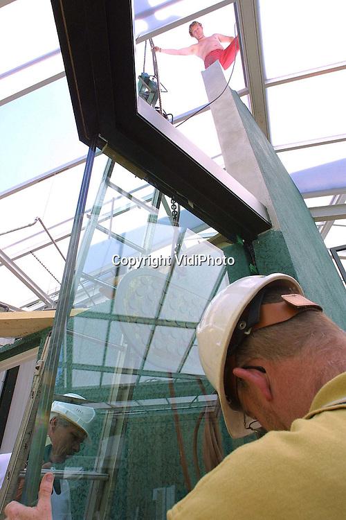 Foto: VidiPhoto..RHENEN - In Ouwehands Dierenpark in Rhenen zijn dinsdagmiddag zowel de enorme glasplaten voor de slangenbak als de metalen vliegtunnel voor Urucu gemonteerd. De glasplaten zijn gevormd uit 3x12 mm dikke lagen en moeten voorkomen dat de giftige anaconda's straks in het publiek terecht komen. Via de vliegtunnel kunnen de enorme vogels van Urucu zich van de ene naar de andere ruimte verplaatsen. Urucu is een overdekt stuk Latijns-Amerikaans oerwoud dat 18 juni gereed moet zijn voor het publiek.