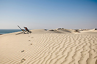 A line of footprints in the sand leads to a pair of deck chairs overlooking the sea