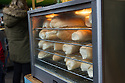 London, UK. 25.10.2014. Bread rolls warming in an oven at a food stall on Borough Market, Southwark. Photograph © Jane Hobson.
