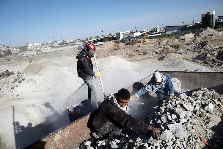 Men force rubble into a crusher at a gravel factory in Gaza. Much of this rubble will have come from Gaza's buffer zone with Israel.