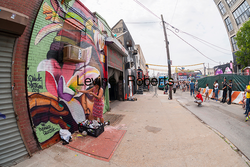 "Danielle Mastrion works on her mural in Bushwick, Brooklyn in New York during the annual Bushwick Collective Block Party on Saturday, June 4, 2016. Music and partying brought some but the real attraction was the new murals  by ""graffiti"" artists that decorate the walls of the buildings that the collective uses.  (© Richard B. Levine)"