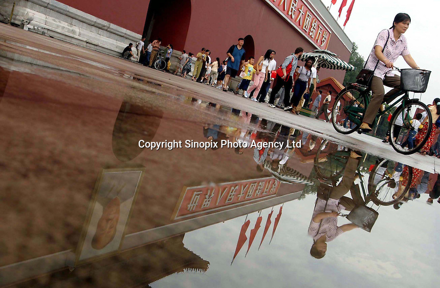 Visitors to Tianamen Square in Beijing are reflected in rain water as they pass under late-Chairman Mao Zedong's portrait..27-JUL-03
