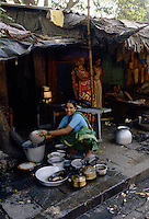 Woman cleans pots and pans at her makeshift homeon the street in Delhi, India.