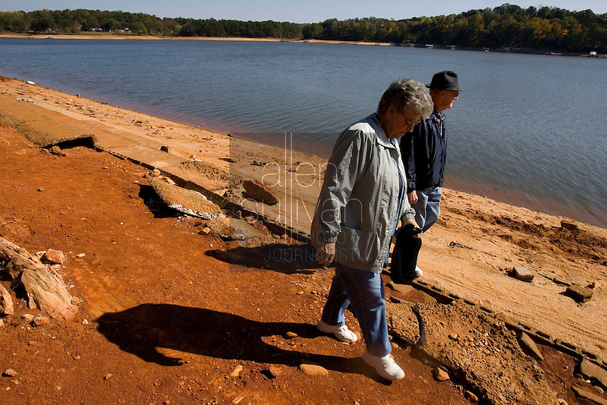 "Lucy and Tolbert Lester walk on the now-exposed grandstands of a submerged race track on Lake Lanier. ""We're just bringing back memories,"" said Mrs. Lester. The couple frequented the track in the 1950s before the area was flooded. The lake provides water for parts of Georgia, Alabama and Florida."