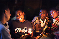 Four brothers, Lawrence (15), Geoffrey (14), Joseph (15) and Deo (12) enjoy a joke over shared school homework before bedtime. The boys, orphaned by AIDS, take it in turns (two at a time) to go to school whilst the other two look for casual work in order to support themselves.<br />