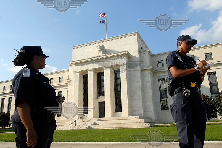 Outside the Federal Reserve building, security officers take down the personal details of a photographer, citing security concerns.