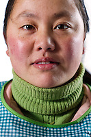 """Worker Yuan Shengping poses for a photograph in in Yiwu factory near Hangzhou, Zhejiang province, China, on February 14, 2012. Yuan Shengping, 26-year-old, comes from Sichuan province: """"I came here to work as the salary here is better than in Sichuan. I left my 2-year-old child in my hometown and my husband takes care of him. I hope I can come back home when my child is of schooling age and that we can build our own house then """". Photo by Lucas Schifres/Pictobank"""