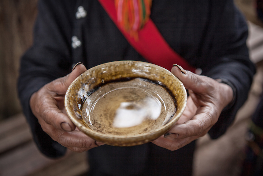 "A Wa woman hold a bowl of local liquor served for the village's guest in Wengding. The Wa, which literally means ""mountain dwellers"", is the hilltribe that inhabit the Sino-Burmese. Known as one of the last headhunting tribe until mid-twentieth century, their population in both countries now approximately no more than one million. In the homogenous society of modern China, Wa is one of more than 50 officially state-recognized ethnic minorities. They can be found around the southwestern corners of Yunnan province."