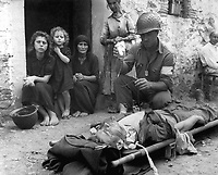Private Roy Humphrey of Toledo, Ohio, is being given blood plasma by Pfc. Harvey White of Minneapolis, Minn., after he was wounded by shrapnel, on 9 August 1943 in Sicily.  Wever. (Army)<br /> NARA FILE #:  111-SC-178198<br /> WAR &amp; CONFLICT BOOK #:  1025
