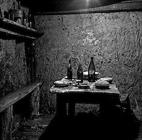 French soldiers' dining area underground with wine bottles, canteens and a serving dish. Photographed 6 December 2011. Vauquois, France.<br />