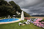 "Portmeirion, in North Wales, is a resort, where no one has ever lived. A self-taught Welsh architect named Sir Clough Williams-Ellis built it out of architectural salvage between the 1920s and 1970s, loosely based on his memories of trips to Portofino. Including a pagoda-shaped Chinoiserie gazebo, some Gothic obelisks, eucalyptus groves, a crenellated castle, a Mediterranean bell tower, a Jacobean town hall, and an Art Deco cylindrical watchtower. He kept improving Portmeirion until his death in 1978, age 94. It faces an estuary where at low tide one can walk across the sands and look out to sea. At high tide, the sea is lapping onto the shores. Every building in the village is either a shop, restaurant, hotel or self-catering accomodation. The village is booked out at high season, with numerous wedding receptions at the weekends. Very popular amongst the English and Welsh holidaymakers. Many who return to the same abode season after season. Hundreds of tourists visit every day, walking around the ornamental gardens, cobblestone paths, and shopping, eating ice-creams, or walking along the woodland and coastal paths, amongst a colourful assortment of hydrangea, rhododendrons, tree ferns and redwoods. The resort boasts two high class hotels, a la carte menus, a swimming pool, a lifesize concrete boat, topiary, pools and wishing wells. The creator describes the resort as ""a home for fallen buildings,"" and its ragged skyline and playful narrow passageways which were meant to provide ""more fun for more people."" It does just that.///The swimming pool with flowering hydrangeas. and the village behind on the hill. the estuary is on the right hand side"