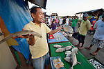 A man hawks fish early in the morning in Tacloban, a city in the Philippines province of Leyte that was hit hard by Typhoon Haiyan in November 2013. The storm was known locally as Yolanda. The ACT Alliance has been active here and in affected communities throughout the region helping survivors to rebuild their homes and recover their livelihoods.